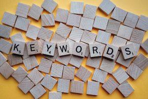 fichas de scrabble formando la palabra keywords. Debes optimizar la búsqueda de palabras clave para mejorar tus posts.